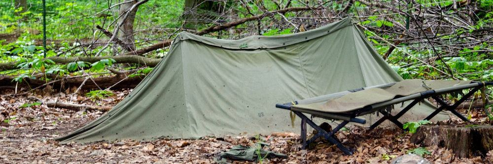 camping-cot-outside-tent-in-woods