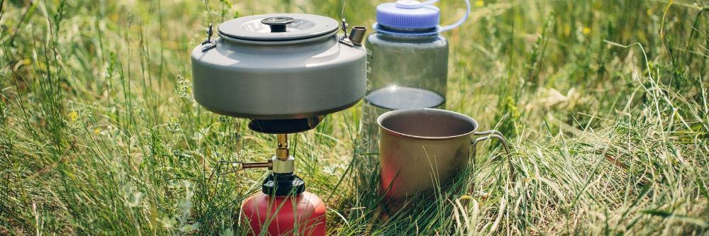 camping-stove-beside-water-bottle-in-grass