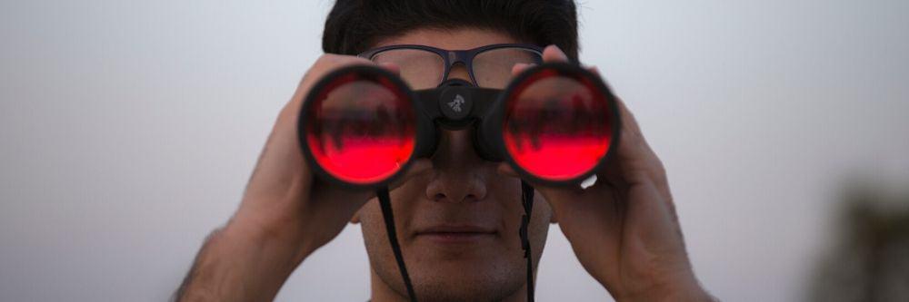 man-holding-red-binoculars