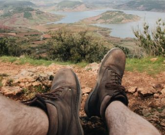 brown-hiking-boots-on-hill