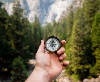 person holding compass while hiking