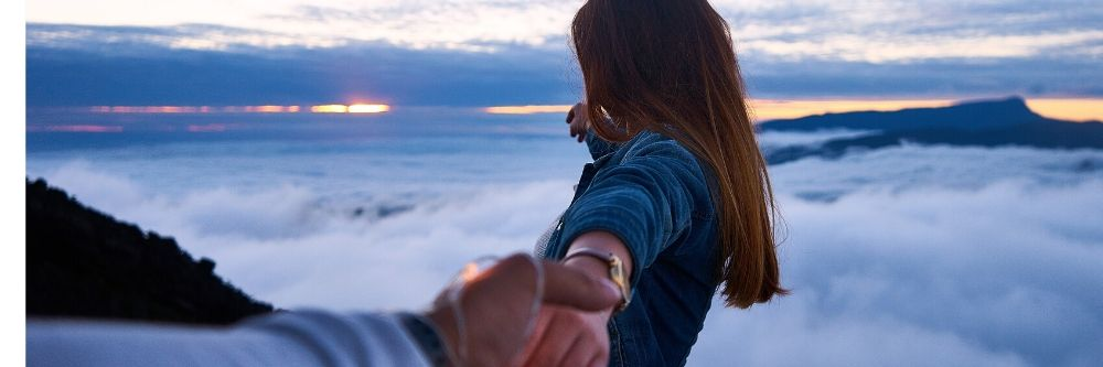 couple holding hands on mountain