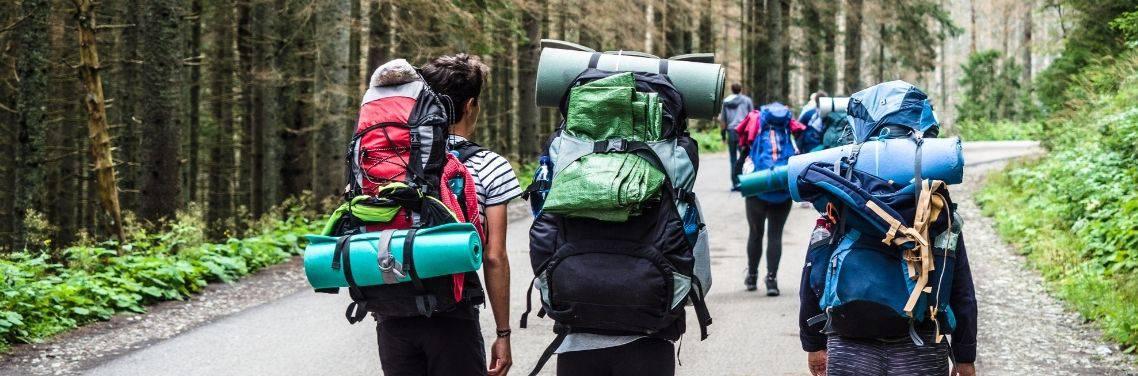 three people hiking with packs